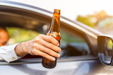 Close up hand hold bottle of beer with sunset background, Dangerous driving concept