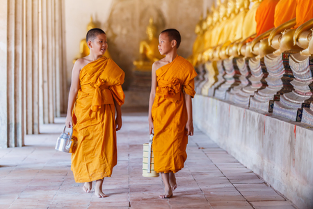 Two novices monk walking and talking in old temple at Ayutthaya Province, Thailand.