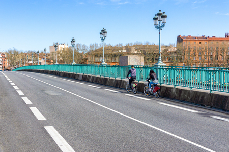People riding a bicycle in a bike lane safely across a city bridge, Toulouse, France