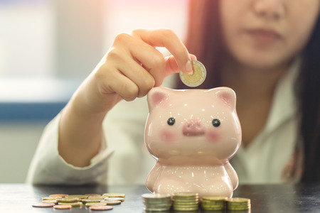 Close up hand female stack euro coins putting in piggy bank, Saving money concept 写真素材