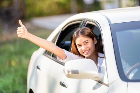 Young Asian woman in white shirt driving her car and showing thumbs up 版權商用圖片