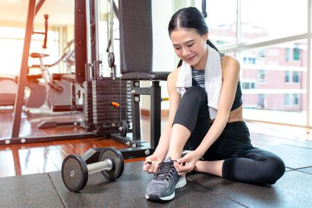Young asian woman wearing running shoes at gym. Fitness and healthy concept