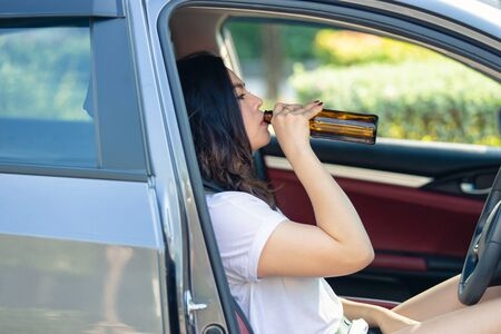 Young asian woman drinking beer while driving a car, Nonthaburi Province, Thailand