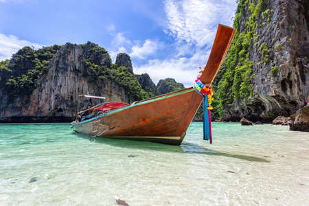 Traditional longtail boat with beautiful scenery view at Pileh Lagoon - Phi Phi Leh Island in sunshine day, Krabi Province, Thailand