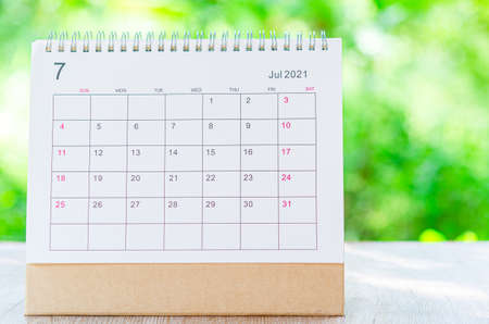 Calendar desk 2021 July month for organizer to plan and reminder on wooden table on nature background.