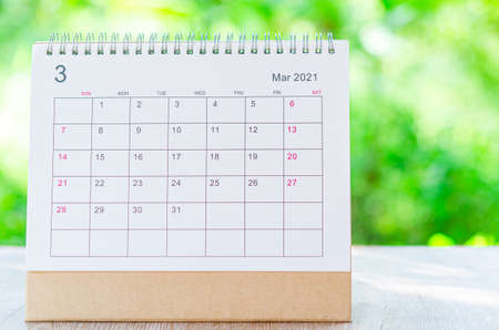 Calendar desk 2021 March month for organizer to plan and reminder on wooden table on nature background.