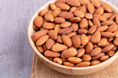 Almonds in wooden bowl on table.