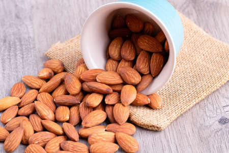 Almonds in bowl on wooden table.