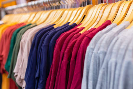 A rack of colorful shirts hanged for sale at local market.