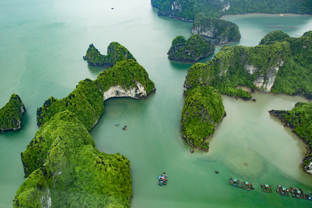 Ha Long Bay, in the Gulf of Tonkin, includes some 1,600 islands and islets, forming a spectacular seascape of limestone pillars. Because of their precipitous nature, Halong bay in sunset, view from above, top view, scenic flight, seaplane, floatplane