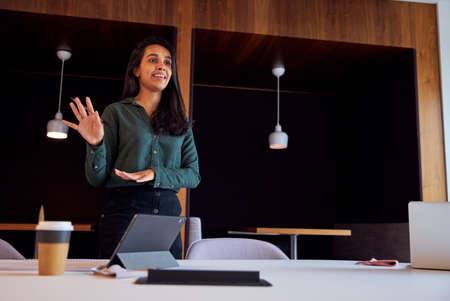 Businesswoman With Digital Tablet Giving Presentation In Modern Open Plan Office