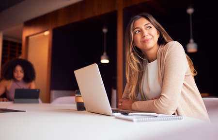 Businesswoman With Laptop At Socially Distanced Meeting In Office During Health Pandemic