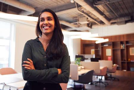 Portrait Of Smiling Businesswoman Standing In Modern Open Plan Office
