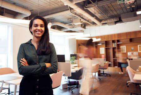 Portrait Of Smiling Businesswoman Standing In Busy Modern Open Plan Office
