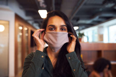 Portrait Of Businesswoman Wearing Face Mask In Modern Open Plan Office During Covid-19 Pandemic