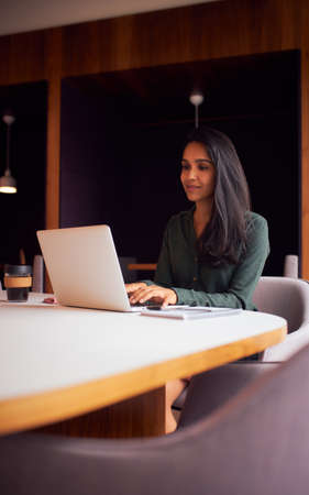 Businesswoman Sitting At Meeting Table Working On Laptop In Modern Open Plan Office