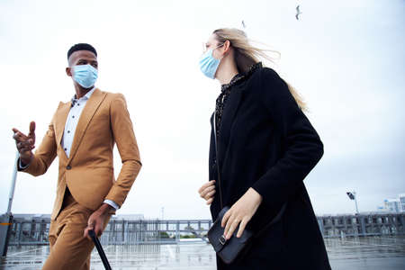 Business Couple Wearing Masks Outside Airport For Business Trip With Luggage During Health Pandemic