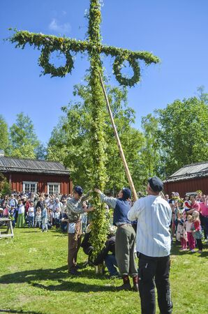 Umea, Sweden - JUNE 23, 2017 Happy people enjoying to watch pole standing moment effort by swedish people and waiting for the swedish mid summer day celebration with colourful environment and blue sky in the background with trees around