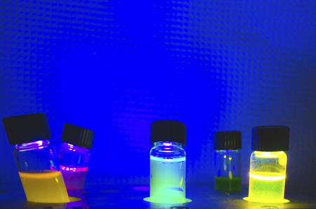 Multiple colourful close up photochemical reaction in glass vial under blue UV light in a dark chemistry laboratory for biomedical research