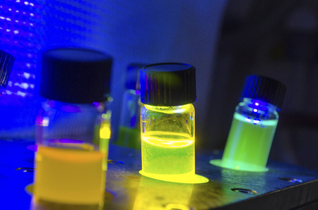 Multiple colourful close up light induced catalyst photochemical reaction in glass vial under UV light in a dark chemistry laboratory for biomedical research
