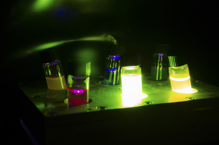 Various colourful light induced catalyst photochemical reaction in glass vials under green light in a dark chemistry laboratory for biomedical research 版權商用圖片