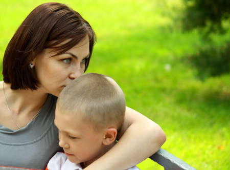 Mother and the son embrace sitting in city park photo