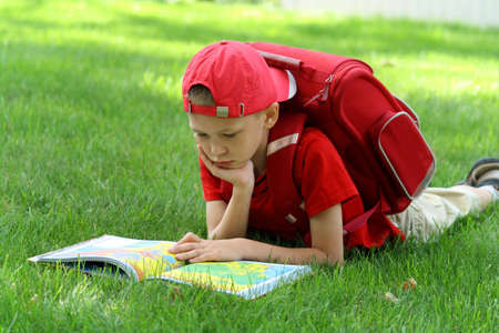 The boy during a school vacation has a rest in a wood reading the book photo