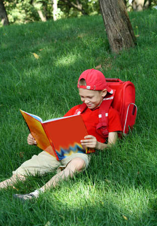 Boy reads the textbook sitting on a grass