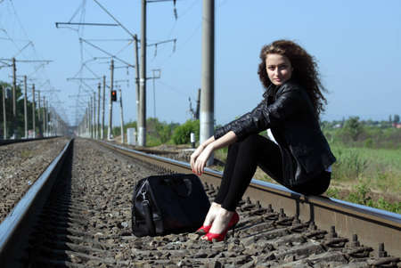 A girl sits on the rail waiting for the train