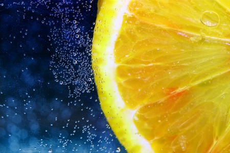 close up of lemon slice under water with small bubbles on dark blue background  photo
