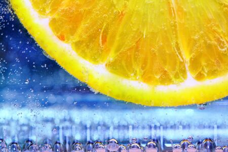 close up of lemon slice under water with bubbles on blue background  photo