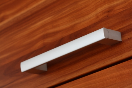 close up of silver furniture handle on wooden drawer photo