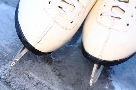 close up of white skates on ice photo