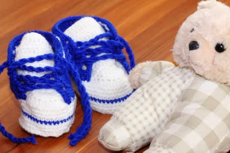 baby blue and white handmade cotton shoes and bear on wooden floor photo