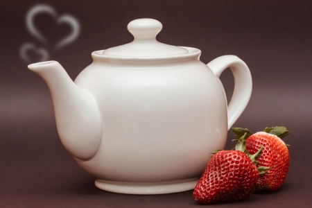 white teapot with hearts and strawberries on black background photo