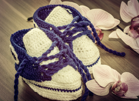 vintage Instagram design - old baby blue and white handmade cotton shoes with orchids on wood floor photo
