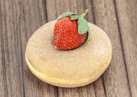 baked sweet donuts with strawberry on desk