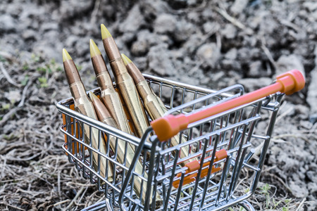 close up of orange chrome shopping cart with bullets on dirty clay