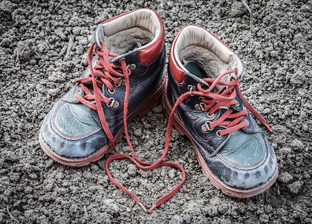 old and dirty little baby booties on clay - heart shaped shoelace photo