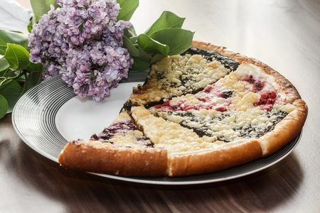 five pieces of sweet pie with plums, cranberries, poppy, curd and blueberries on plate with lilac flower named Wallachian Frgal
