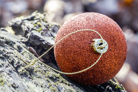 close up of orange Christmas bauble lying on a rock