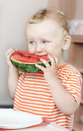 little boy holding and eating a fresh watermelon photo