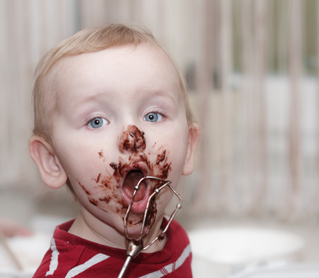 messy eater: chocolate on face, funny cute eating boy, messy eater