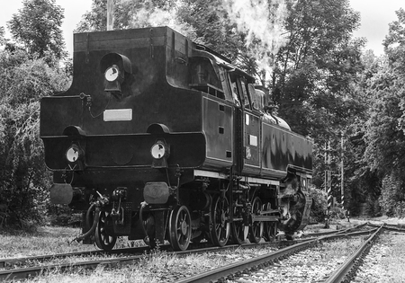 narrow gauge railways: black and white retro style photo of steam locomotive on the tracks (made in the Czech Republic 1948 - Matej, number 433002) Stock Photo