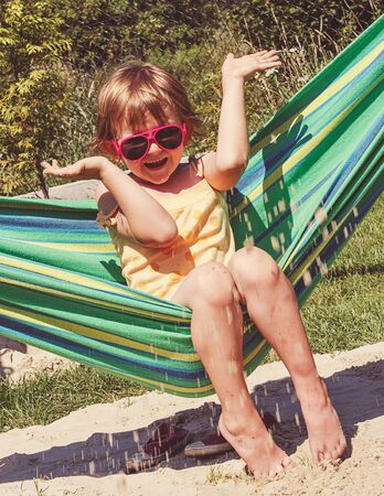 frolicking: summer time - little girl with sun glasses on a hammock frolicking with sand - vintage retro style image Stock Photo