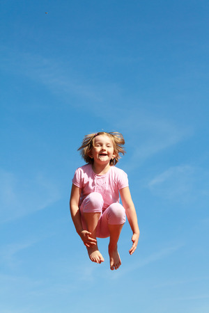 cute young girl jumping over blue sky