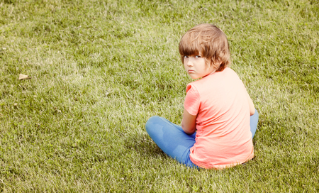 offended: offended young girl sitting on the grass