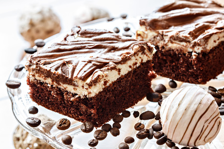 two dark pieces of filled cake with chocolate icing and coffee beans Stock Photo