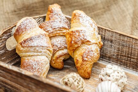 close up of three croissants in the wooden bowl