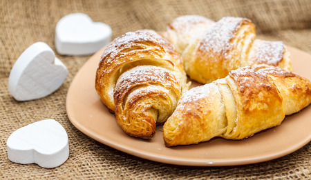close up of three croissant baked with love on plate
